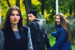 Άπιστο άτομο που περπατά με τη φίλη και που εξετάζει κατάπληκτο ένα άλλο σαγηνευτικό κορίτσι Στοκ Φωτογραφίες