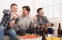 Άπληστα gamers Συγκινημένα άτομα που παίζουν τα τηλεοπτικά παιχνίδια στο σπίτι στοκ φωτογραφία