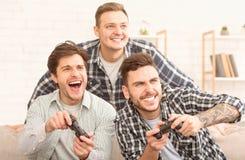 Άπληστα gamers Συγκινημένα άτομα που παίζουν το τηλεοπτικό παιχνίδι στοκ φωτογραφίες