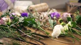 Άποψη άνωθεν: ξύλινος πίνακας με τα λουλούδια, ψαλίδι, ταινίες, διακοσμώντας το έγγραφο και άλλα εργαλεία για τη ρύθμιση ανθοδεσμ απόθεμα βίντεο