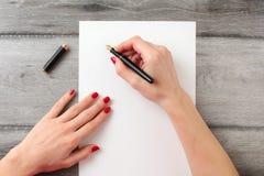 Άποψη άνωθεν στα χέρια γυναικών ` s με τα κόκκινα καρφιά, που κρατούν το μαύρο φ στοκ εικόνες