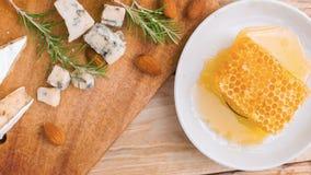Άποψη άνωθεν σχετικά με έναν αγροτικό πίνακα με το μέλι, το τυρί και τα καρύδια απόθεμα βίντεο