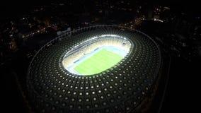 Άποψη άνωθεν σχετικά με το καταπληκτικό φωτισμένο γήπεδο ποδοσφαίρου στη νύχτα, πόλη απόθεμα βίντεο