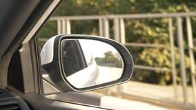 Άποψη έξω ο οπισθοσκόπος καθρέφτης, όταν περνά το αυτοκίνητο κατά μήκος του δρόμου το καλοκαίρι 4k, σε αργή κίνηση πυροβολισμός φιλμ μικρού μήκους