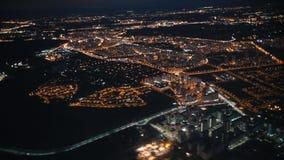 Άποψη από ένα αεροπλάνο έξω το παράθυρο της πόλης Φω'τα νύχτας δεμένη όψη σκαφών λιμένων νύχτας φιλμ μικρού μήκους