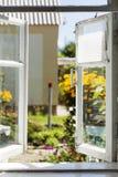 Άποψη από ένα παλαιό αγροτικό παράθυρο σε ένα ηλιόλουστο θερινό προαύλιο Στοκ Εικόνα