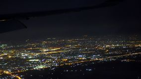 Άποψη από ένα παράθυρο του επιβάτη του αεροπλάνου Όμορφοι ανοιχτοί χώροι της πόλης που γεμίζουν με τις πυρκαγιές νύχτας Το αεροπλ φιλμ μικρού μήκους