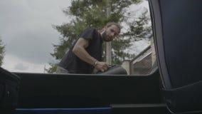 Άποψη από μέσα από τον κορμό αυτοκινήτων των χιλιετών τσαντών ταξιδιού φόρτωσης ατόμων στο αυτοκίνητο μποτών που προετοιμάζεται γ απόθεμα βίντεο