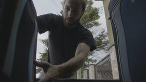 Άποψη από μέσα από το αυτοκίνητο του χαρούμενου νέου περιστασιακού ατόμου που φορτώνει τις βαριές αποσκευές στον κορμό που πηγαίν απόθεμα βίντεο