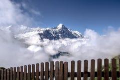 Άποψη από πίσω από το φράκτη στο βουνό Eiger που περιβάλλεται από τα σύννεφα στοκ φωτογραφίες