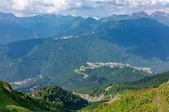 Άποψη από τα ύψη της κοιλάδας από τα κατοικημένα σπίτια, που περιβάλλονται από τα υψηλά βουνά Krasnaya Polyana, Sochi στοκ φωτογραφία