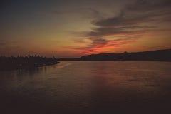 Άποψη από τη γέφυρα πέρα από τον ποταμό σε ένα καταπληκτικό ηλιοβασίλεμα με τα φωτισμένα σύννεφα Στοκ Εικόνες