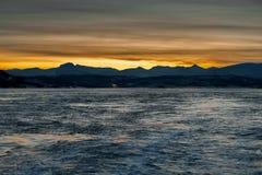 Άποψη από τη θάλασσα στον ήλιο ρύθμισης πίσω από τα βουνά Σκοτεινή ώρα της ημέρας Στοκ Φωτογραφία