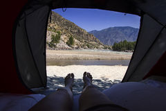 Άποψη από τη σκηνή τουριστών μέσα στο τοπίο βουνών με τον ποταμό πόδια γυναίκας στα βουνά στοκ φωτογραφία με δικαίωμα ελεύθερης χρήσης