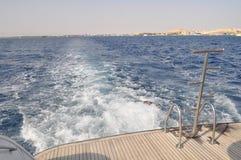 Άποψη από το γιοτ στα κύματα και την κυανή ακτή με την άσπρη άμμο, το καθαρό και σαφές μπλε νερό μια ηλιόλουστη ημέρα Στοκ εικόνα με δικαίωμα ελεύθερης χρήσης