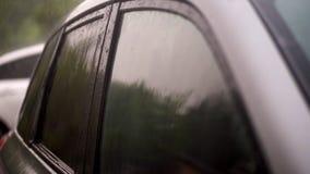 Άποψη από το εξωτερικό, υπάρχει δυνατή βροχή, ντους, πτώση πτώσεων στα βαμμένα παράθυρα του κενού μαύρου αυτοκινήτου που στέκεται απόθεμα βίντεο