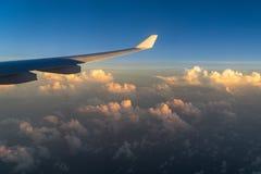 Άποψη από το παράθυρο αεροπλάνων με τα σύννεφα στο ηλιοβασίλεμα και το φτερό αεροπλάνων Στοκ Εικόνες