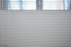 Άποψη από το παράθυρο μέσω των όχι εντελώς κλειστών τυφλών στοκ εικόνα με δικαίωμα ελεύθερης χρήσης