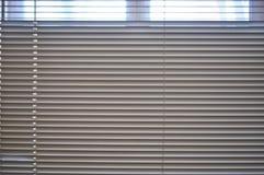 Άποψη από το παράθυρο μέσω των όχι εντελώς κλειστών τυφλών στοκ φωτογραφία