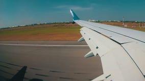 Άποψη από το παράθυρο στο φτερό ενός αεροπλάνου που πετά χαμηλά στο έδαφος και προσγείωση στον αερολιμένα απόθεμα βίντεο