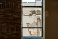 Άποψη από το παράθυρο του σύγχρονου κτηρίου στην πρόσοψη του παλαιού κτηρίου με τη στήλη Στοκ Εικόνες