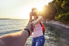Άποψη από το πρώτο πρόσωπο ενός ατόμου που κρατά ένα χέρι κοριτσιών ` s με μια κάμερα φωτογραφιών στην ακτή Στοκ φωτογραφία με δικαίωμα ελεύθερης χρήσης