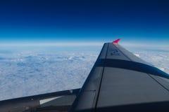 Άποψη από το φωτιστικό αεροπλάνων Η άποψη από το παράθυρο του αεροπλάνου στο φτερό, τα σύννεφα και το μπλε ουρανό στοκ φωτογραφία με δικαίωμα ελεύθερης χρήσης