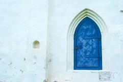 Άποψη αρχιτεκτονικής των στοιχείων αρχιτεκτονικής - ηλικίας σκούρο μπλε σφυρηλατημένη μέταλλο πόρτα με το arcade στον άσπρο τοίχο Στοκ εικόνες με δικαίωμα ελεύθερης χρήσης