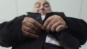 Άποψη βάσεων του παχουλού ατόμου στο κλασικό κοστούμι που στερεώνει ένα κουμπί στο σακάκι του, κινηματογράφηση σε πρώτο πλάνο απόθεμα βίντεο