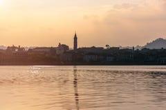 Άποψη βραδιού της πόλης από τη λίμνη Σκιαγραφία της πόλης στο ηλιοβασίλεμα Ιταλία, Arona τονισμός Στοκ Εικόνα