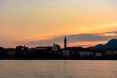 Άποψη βραδιού της πόλης από τη λίμνη Σκιαγραφία της πόλης στο ηλιοβασίλεμα Ιταλία, Arona τονισμός Στοκ Εικόνες