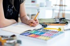 Άποψη γωνίας κινηματογραφήσεων σε πρώτο πλάνο ενός θηλυκού σχεδίου σχεδίων ζωγράφων στο sketchbook που χρησιμοποιεί το μολύβι Καλ Στοκ Εικόνες