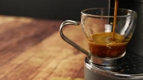 Άποψη γωνίας στενού επάνω του ιταλικού καφέ espresso Το χέρι μιας γυναίκας στηρίζεται το φλυτζάνι γυαλιού κάτω από τα αεριωθούμεν απόθεμα βίντεο