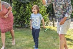 Άποψη ενός αγοριού 6 ποιος αναμένει με ενδιαφέρον τους ενηλίκους ρολογιών κήπων που παίζουν ένα παιχνίδι σφαιρών Στοκ Εικόνα