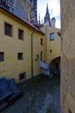 Άποψη ενός κίτρινου κατασκευασμένου κτηρίου με μια στενή οδό τούβλου μέσα - μεταξύ Στοκ Φωτογραφίες