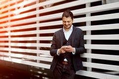 Άποψη ενός νέου ελκυστικού επιχειρησιακού ατόμου που χρησιμοποιεί το smartphone υπαίθρια Στοκ Φωτογραφία