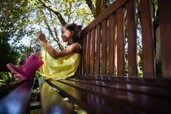 Άποψη επιπέδων επιφάνειας του χαμογελώντας κοριτσιού που χρησιμοποιεί το κινητό τηλέφωνο καθμένος στον ξύλινο πάγκο στοκ φωτογραφία με δικαίωμα ελεύθερης χρήσης
