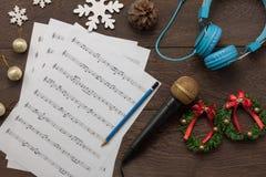 Άποψη επιτραπέζιων κορυφών της Χαρούμενα Χριστούγεννας σημειώσεων και εξαρτημάτων φύλλων μουσικής & της έννοιας καλής χρονιάς Στοκ Εικόνες