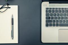 Άποψη επιτραπέζιων κορυφών του lap-top και του σημειωματάριου στον εκλεκτής ποιότητας τόνο στοκ φωτογραφίες