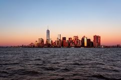 Άποψη ηλιοβασιλέματος οριζόντων πόλεων της Νέας Υόρκης από τη βάρκα στο νησί του Ellis στοκ εικόνα