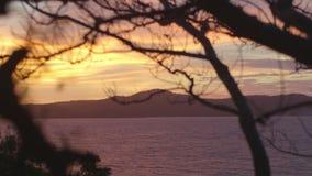 Άποψη ηλιοβασιλέματος της θάλασσας με τους λόφους απόθεμα βίντεο