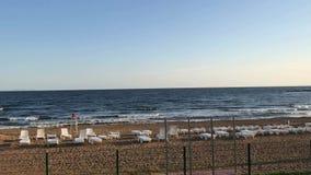 Άποψη θάλασσας με μια αμμώδη παραλία στο πρώτο πλάνο και έναν σαφή ουρανό στο υπόβαθρο απόθεμα βίντεο
