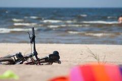 Άποψη θάλασσας παραλιών με το ποδήλατο, τους κολυμπώντας ανθρώπους και την πετσέτα στοκ φωτογραφίες