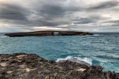 Άποψη θάλασσας σημείου Laie του βράχου με μια τρύπα πριν από το ηλιοβασίλεμα με το σκοτεινό γκρίζο ουρανό στοκ εικόνα με δικαίωμα ελεύθερης χρήσης