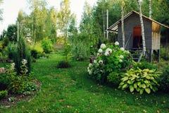 Άποψη κήπων χώρας με το ξύλινο σπίτι Στοκ Φωτογραφία