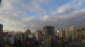 Άποψη καμπυλών σχετικά με τα άσπρα αυξομειούμενα σύννεφα στον ουρανό επάνω από την πόλη απόθεμα βίντεο