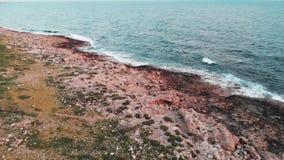 Άποψη κηφήνων των μεγάλων ωκεάνιων κυμάτων με το νέο καυκάσιο περπάτημα κοριτσιών μέσω της δύσκολης παραλίας απόθεμα βίντεο