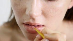 Άποψη κινηματογραφήσεων σε πρώτο πλάνο ενός επαγγελματικού καλλιτέχνη makeup που εφαρμόζει το κραγιόν στα πρότυπα χείλια ` s που  απόθεμα βίντεο