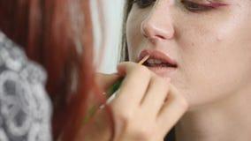 Άποψη κινηματογραφήσεων σε πρώτο πλάνο ενός επαγγελματικού καλλιτέχνη makeup που εφαρμόζει το κραγιόν στα πρότυπα χείλια ` s που  φιλμ μικρού μήκους