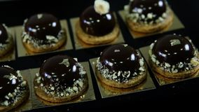 Άποψη κινηματογραφήσεων σε πρώτο πλάνο σχετικά με τα μικρά στρογγυλά επιδόρπια σοκολάτας απόθεμα βίντεο